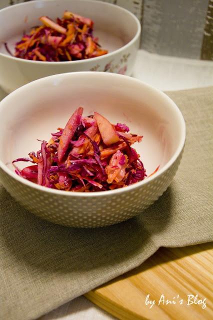Zwei Schüsseln voll mit leckerem Rotkohlsalat, Apfelspalten und Möhrenraspeln.