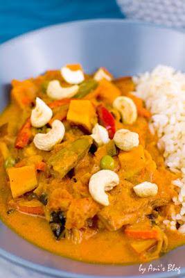 Ein Teller voller feurigem veganem Gemüsecurry mit Süßkartoffeln, Wokgemüse, Kokosmilch und Cashewkernen, dazu Reis.