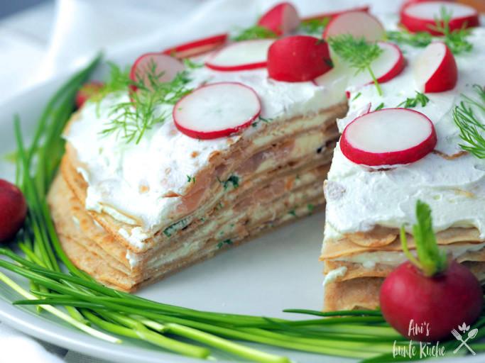 Schichten der angeschnittenen Lachs Crepes Torte auf Schnittlauchbett