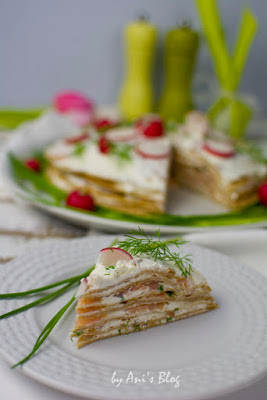 Ein Stück Räucherlachs-Crepes-Torte mit Dillspitzen