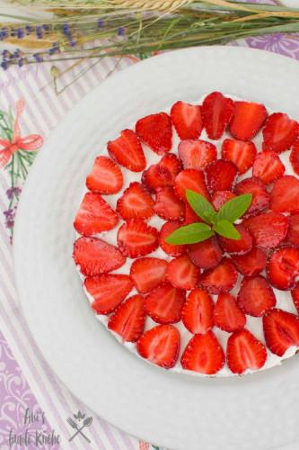 vegane Erdbeertorte mit Kokoscreme und rot leuchtenden Erdbeeren.