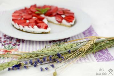 Sommerliche Erdbeertorte mit Kokosfüllung auf mit Wildblumen geschmückten Tisch