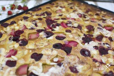 Rhabarberkuchen vom Blech. Dazu kommen Himbeeren und Erdbeeren.