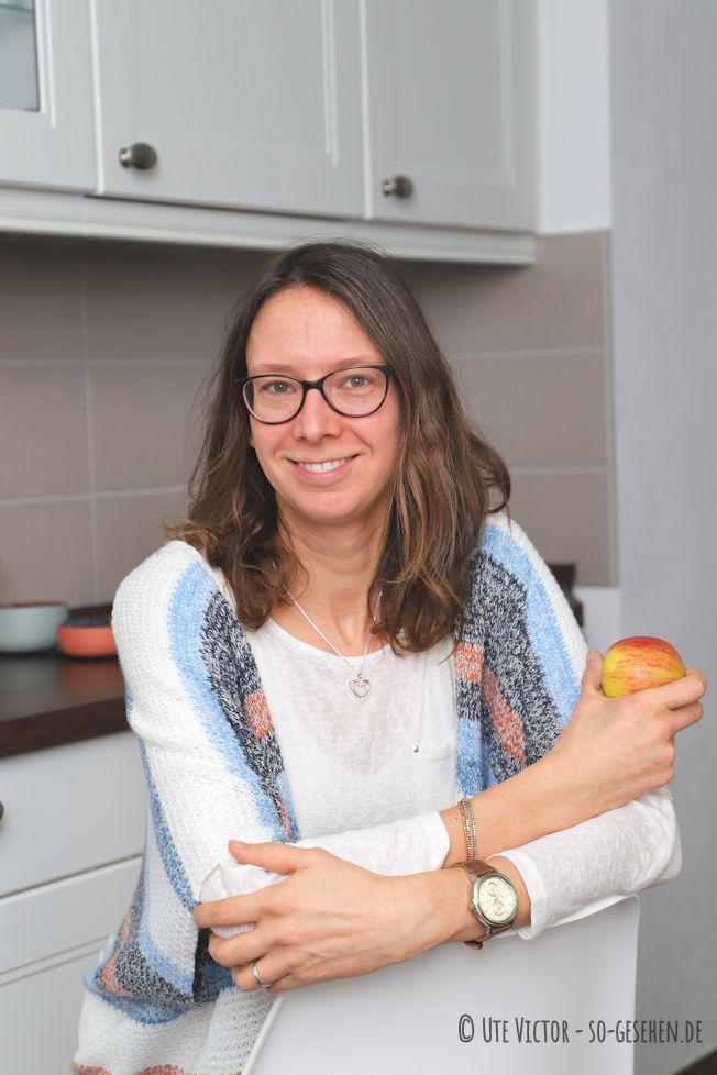 Frau sitz mit Apfel in der Hand in der Küche.